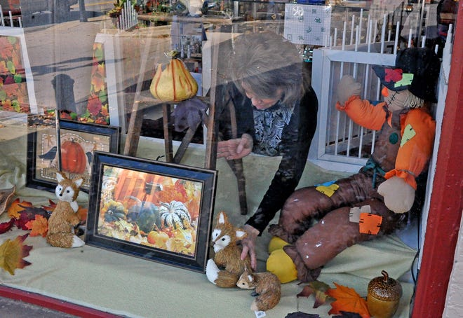 Linda Gaumer of the The Gift Corner, located on the southwest corner of the Wooster's downtown square, sets up her fall window display for Saturday's Fall Shop Hop.