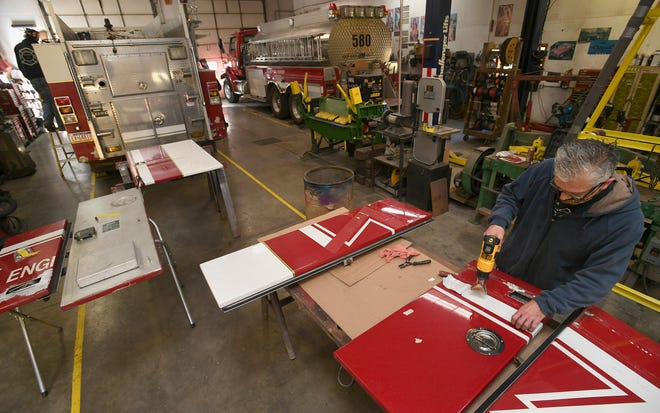 Dennis Webber, 37, upper left, and Ralph Chamberlain, 48, bottom right, work on a fire engine Oct. 16 at Fire-Fly Fire Equipment Sales Inc. in Platea. The family-owned company provides fire equipment and service to fire departments throughout the tri-state area.