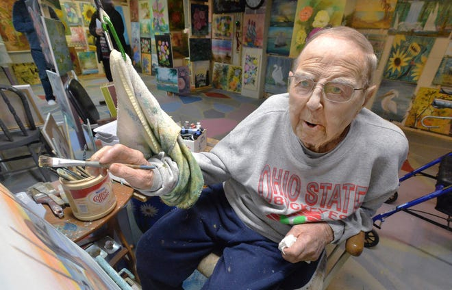 Jack Cryder, 95, is a former art teacher and academic administrator who found more time to paint in his retirement. Cryder uses a towel and pulley system to help with fatigue in his brush hand as he paints in his basement studio on Oct. 20, 2020, in Albion.