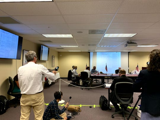 Jim Piggott (left) objects to wrestling board chairman Brent Shore (in front of the screen) and tells Piggott and others to stop recording.