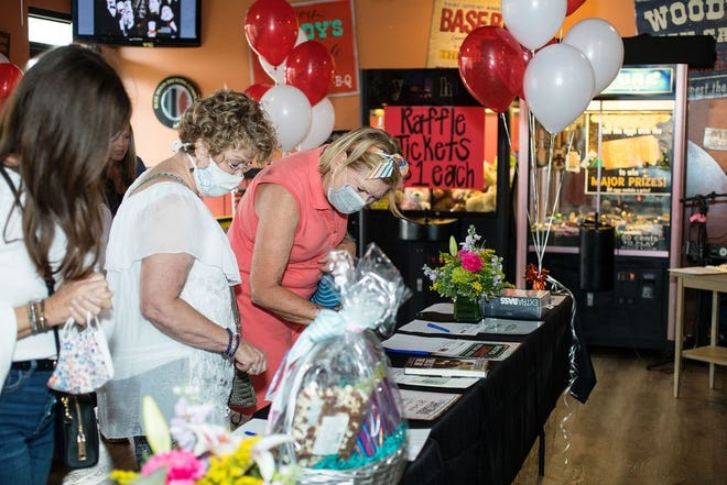 Attendees peruse silent auction items at the Woody's-Bar-B-Q 40th anniversary benefit celebration Oct. 3 in Ponte Vedra Beach.