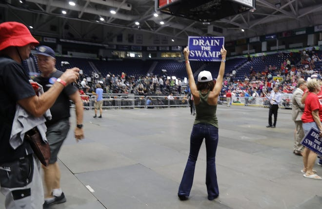 "Brittany Webb, of Marco Island, displays a ""Drain The Swamp"" sign during a Make America Great Again rally by President Donald Trump in Fort Myers."