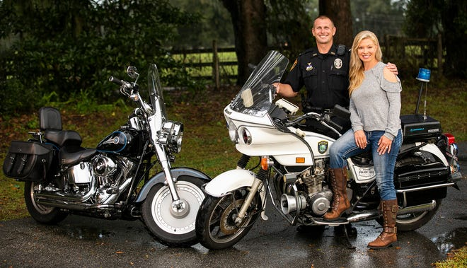 Ocala Police Department Lt. Eric Hooper and his wife, Barbara, pose with his restored 1989 vintage Kawasaki KZ1000 motorcycle dressed out in OPD trim at their home in Citra.