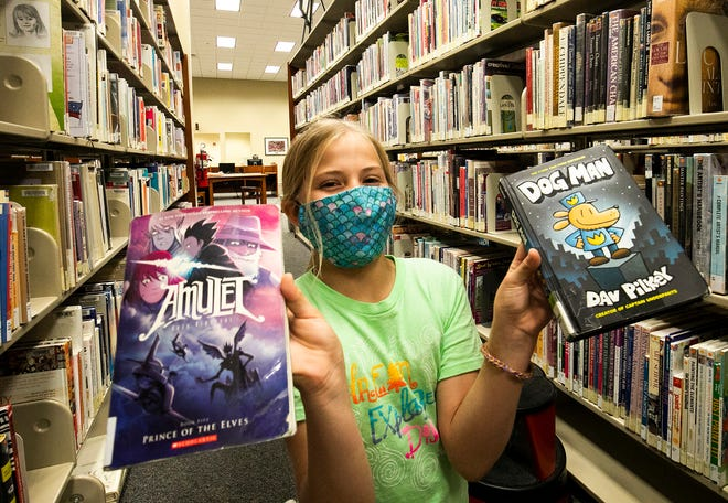 Ariana Pierce, 10, shows off two of the books that she planned on checking out at the Marion County Public Library Headquarters on Oct. 21