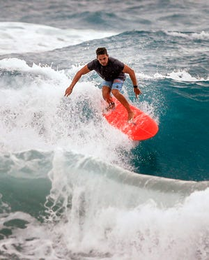 """A surfer rides a wave at Midtown beach Wednesday morning as rain drizzles in the area, October 21, 2020. The sign at the beach read, """"High Bacteria, Strong Rip Currents, Rough Surf."""" (DAMON HIGGINS / THE PALM BEACH DAILY NEWS)"""
