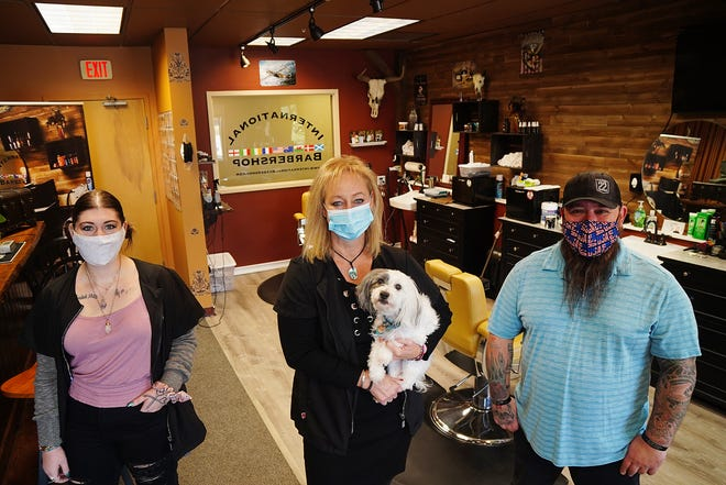 Barbers at the International Barbershop in Machester Square at Pease, including Jessica Hamilton, Tammie Lassonde, holding Murphy the dog, business owner, and Chad Kozdra, are concerned about their business as so many of the Tradeport employees continue to work remotely from home.