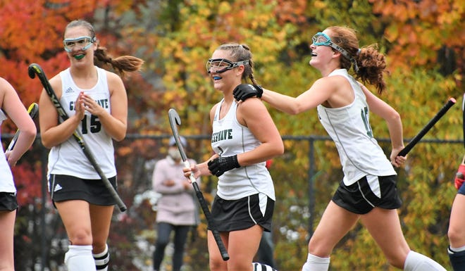 Dover High School's Jeannine Turgeon, center, celebrates her second goal with teammates Charlotte Morin, left, and Meghan Fitzgerald on Wednesday during the Division I field hockey playoffs. Dover beat Exeter, 3-1.