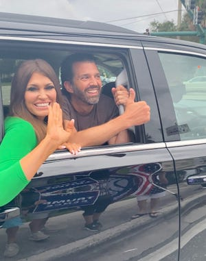 Campaign adviser Kimberly Guilfoyle, left, and Donald Trump Jr. drive past supporters of the president in Jupiter on Wednesday.