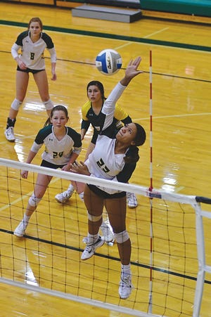 Pratt High School junior Sierra Dunlap spikes the ball with teammates ready to cover.