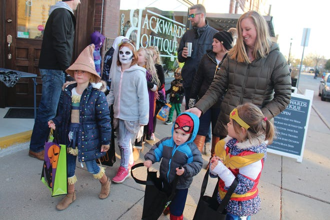 Kids and families pick up treats from downtown businesses during the 2019 Spooktacular event.