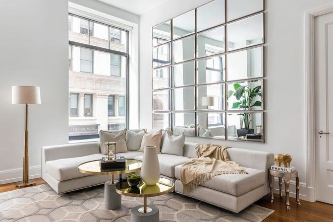 20 identical mirrors hung in a grid pattern makes an impressive statement in this living room.