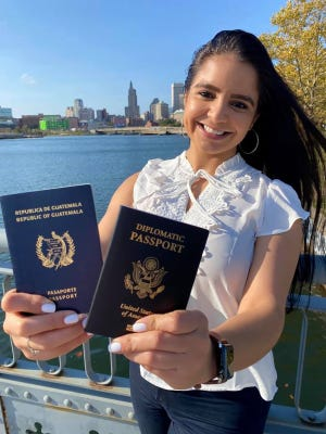 Marta Aparicio, who overcame poverty in Guatemala and Providence to become a U.S. diplomat, shows her old passport, where her journey began, and her new State Department-issued diplomatic passport.
