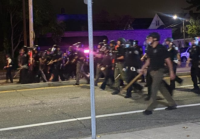 Police face protesters on Elmwood Avenue on the Providence/Cranston line Wednesday night. The family of Jhamal Gonsalves have shunned the violence that has erupted since he was gravely injured in a moped crash.
