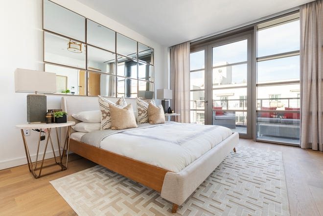 Mirrors in a pattern help extend the ceiling height in this master bedroom.