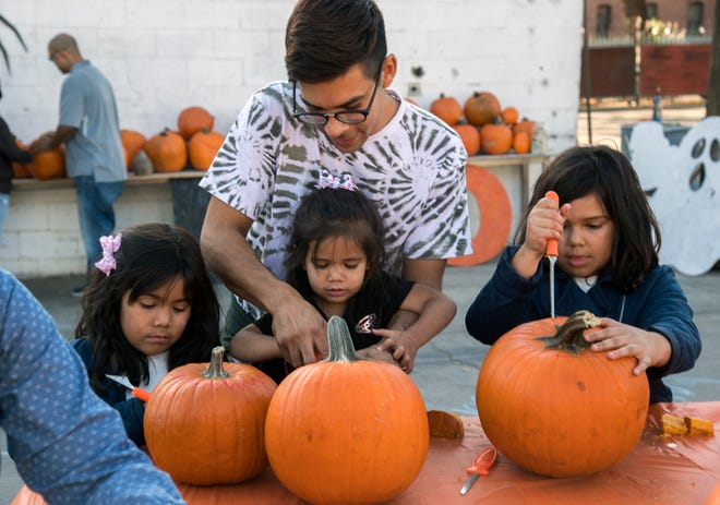 Eric Lujan helps his daughters, Amelia, left, Holly and Winnie as they carve their jack-o-lanterns at the pumpkin-carving and painting workshop at the HATCH Workshop in downtown Stockton in 2019.
