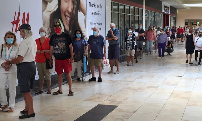 Voters line up at an early voting polling place at Sarasota Square Mall on Thursday. Early voting in Florida continues through Sunday.