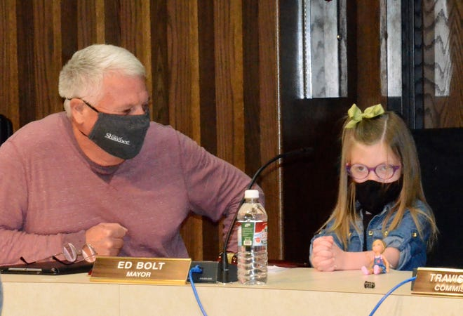 Shawnee resident Kennedy Allison, 4, and her doll wait patiently to call the Shawnee City Commission meeting to order as Mayor Ed Bolt supervises.