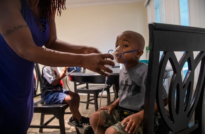 Vanisha Williams, left, adjust a nebulizer mask on the face of her 4-year-old son Jonathan, right, as he and his twin brother Jeremiah receive nebulizer treatments for asthma at their home in Bayboro Thursday, Aug. 20, 2020. Eastern North Carolina has more people making trips to hospital emergency departments for asthma treatments than in any other part of the state, researchers at East Carolina University reported.