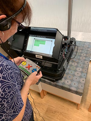 A voter practices using the assistive voting machine. The equipment helps those with vision impairments cast a ballot. The machines will be available at all six of Alachua County's early-voting sites, and on Election Day.