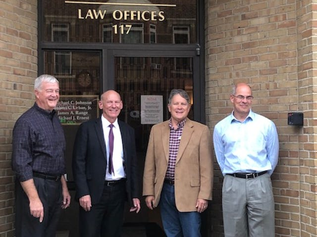 James Range, Robert Urban, Michael Johnson and Michael Ernest (left to right) are shown at the entrance to the Johnson, Urban & Range Co. law office in New Philadelphia. The office closed Oct. 14.