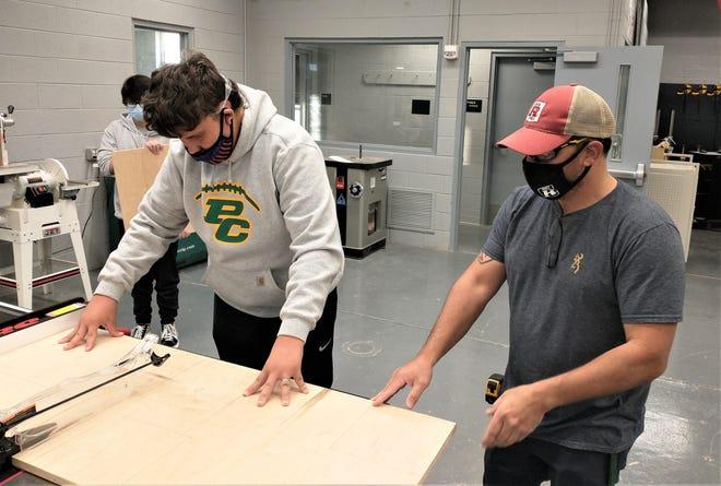 Pueblo County High School Hornet Wayde Vialpando, left, receives instruction on the use of a table saw from teacher Rex Harriman.