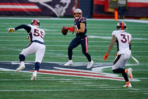 New England Patriots wide receiver Julian Edelman, center, looks for a receiver as he attempts to pass between Denver Broncos linebacker Bradley Chubb, left, and safety Justin Simmons, right, in the second half on Sunday in Foxborough, Mass. (AP Photo/Charles Krupa)