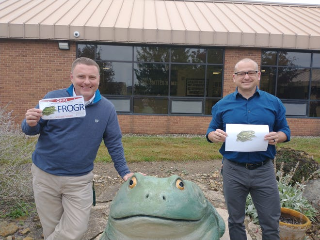 Grizzell Middle School teachers Shawn Kaeser (left) and Todd Arnold stand in the school courtyard with a frog statue purchased by the Grizzell parent-teacher organization in 2010 in recognition of Dublin City Schools students' efforts in making the bullfrog the state frog. Kaeser is holding a mockup of how a new state license plate with the bullfrog might look, and Arnold is holding a print of the digital sketch he made for use on the plate.
