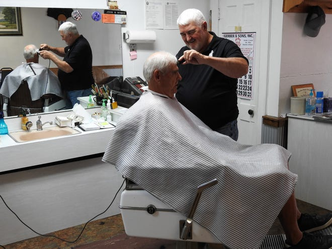 John McKee cuts the hair of Steve Donley, a longtime customer of McKee's Barber Shop on Third Street. McKee is retiring Friday after 57 years as a barber at the age of 80.
