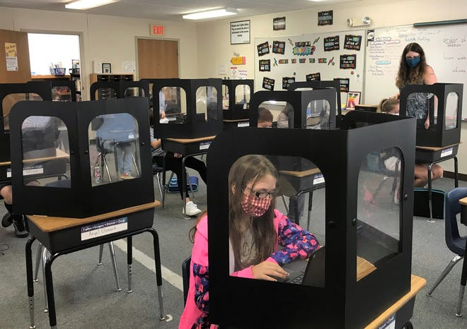 Students in a fourth grade classroom working during the day behind barriers and wearing masks at Keene Elementary School, part of the River View district. Keene was hit hard with not only COVID-19 pandemic protocols this school year, but cuts to staff due to loss funding.