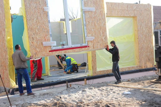 Contractors install modular frame plywood board panel walls house on the home construction site in 2018 in Kyiv, Ukraine. Oriented Strand Board now fetches a higher price as increased demand and tight supplies lead to delivery delays and elevated construction costs in the U.S. and Canada. (Oleksandr Rado/Dreamstime/TNS)