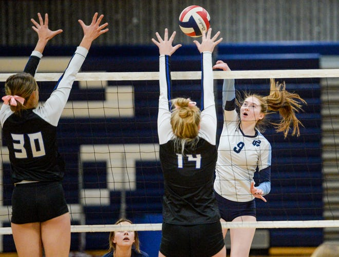 Great Falls High's Kendal Burcham spikes against Skyview defenders Brooke Berry, left and Emily Schultz in Wednesday's volleyball match in the Swarthout Fieldhouse.