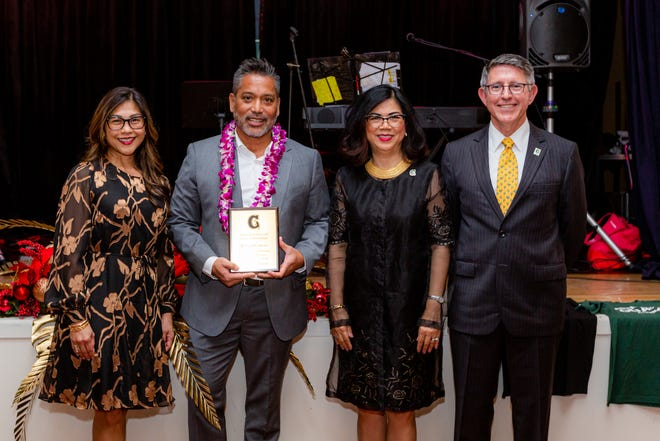 Roland Certeza, president and CEO of GTA, holds his University of Guam Distinguished Alumni Award at last year's All-Class UOG Alumni Reunion, held Nov. 23 at the Lotte Hotel Guam. From left: Annette T. Santos, dean of the UOG School of Business and Public Administration; Certeza; Anita Borja Enriquez, UOG senior vice president and provost; and Thomas W. Krise, UOG president.