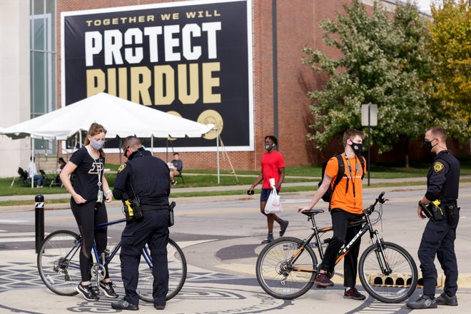 Purdue University Police Officers Aaron Pitts, left, and Stephen Puckett issue warnings to two cyclists that failed to stop at an intersection, Thursday, Oct. 22, 2020 in West Lafayette. PUPD is targeting cyclist and electric and motor-powered vehicles traffic violations.