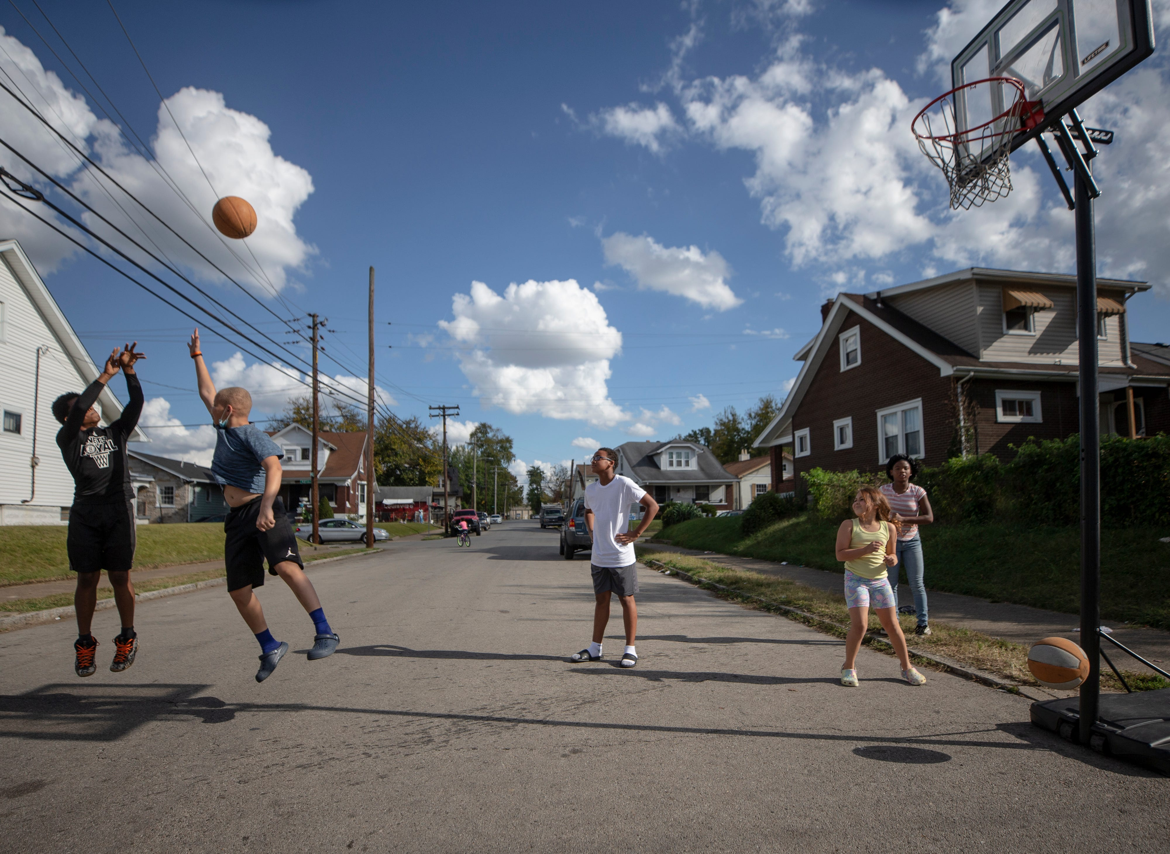 Chris Miller, 13, right, gets off a shot against Kentrelle Bell, 13, while playing basketball on Herman Street in Louisville's Shawnee neighborhood on Oct. 22, 2020.