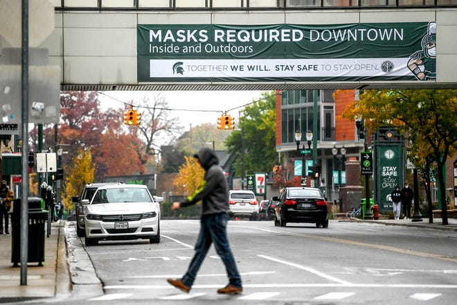 A sign reminds people downtown to wear masks inside and outside on Thursday, Oct. 22, 2020, in East Lansing.