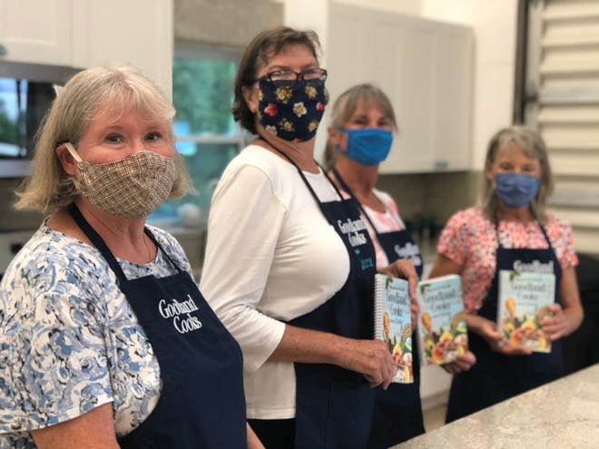 Wearing face masks, Goodland Civic Association's arts committee members Linda Van Meter, Tara O'Neill, Celeste Navara and Judy Wittwer hold copies of Goodland Cooks and Chills at Goodland Community Center on Oct. 16, 2020.