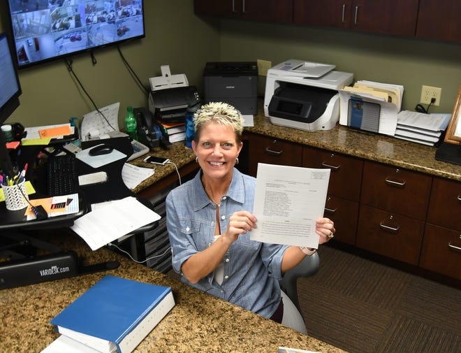 Baxter County Tax Collector Teresa Smith holds a copy of the order from Pulaski County Circuit Court Judge Tim Fox discontinuing the collection of a yearly $18 solid waste fee that has appeared on landowners' property tax statements for the past three years. The fee will cease being collected beginning with the 2020 tax statements, which will be mailed out next year.