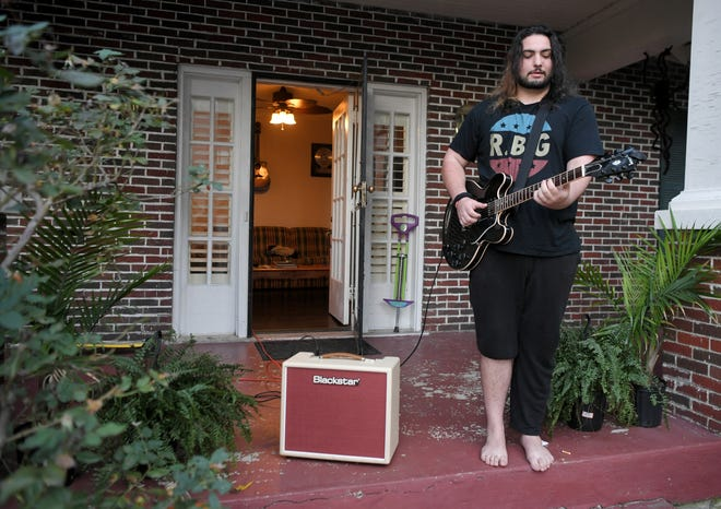 Musician Rocco Cipriano plays on his front porch across from Belmont University before the final Presidential Debate between President Donald Trump and former Vice President Joe Biden Thursday, Oct. 22, 2020, in Nashville, Tenn.