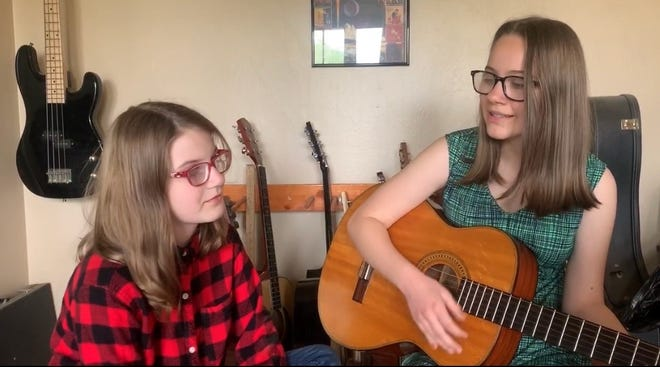 Abigail Munyon, right, and Kaylee Munyon, left, play guitar and sing together. Abigail is a 2020 Tulare County Office of Education Character Counts! Award recipient.