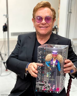 Elton John poses with his new Barbie doll.
