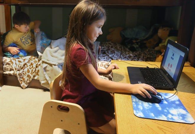 Milania McClure works on her online kindergarten class Oct. 20 in Akron.