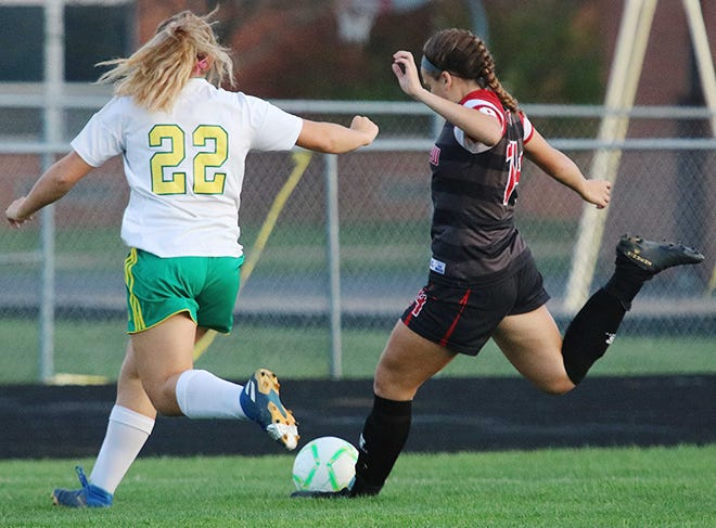 Crestview's Mary Leeper (14) sends a shot toward the goal as Cory-Rawson's Brynn Reese (22) defends during a Division III sectional final game at Crestview High School. The Cougars won, 3-2.