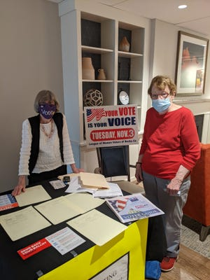 Wesley Enhanced Living residents Madeline Rawley (left) and Mary Ellen Brehm stand beside the voting information booth at the Doylestown long-term care facility.