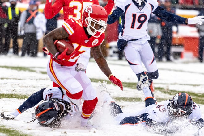 Chiefs wide receiver Mecole Hartman tries to avoid Broncos defenders in a game last December.