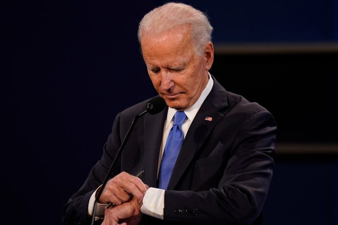 Former Vice President Joe Biden checks his watch Thursday during the second and final presidential debate with President Donald Trump at Belmont University in Nashville, Tenn.