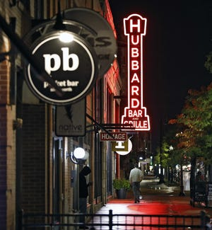 A customer walks by Hubbard Bar and Grill in the Short North in Columbus. Bars and restaurants have been linked to some COVID-19 cases and outbreaks.