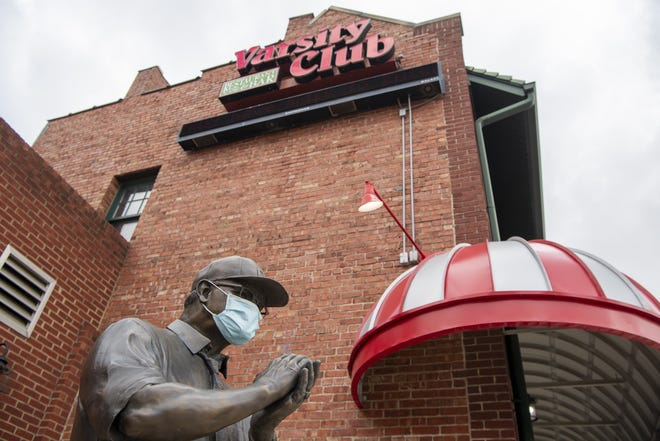 The Woody Hayes statue, adorned with a mask, stands next to the Varsity Club on West Lane Avenue, a normally popular destination on Buckeye football game days.