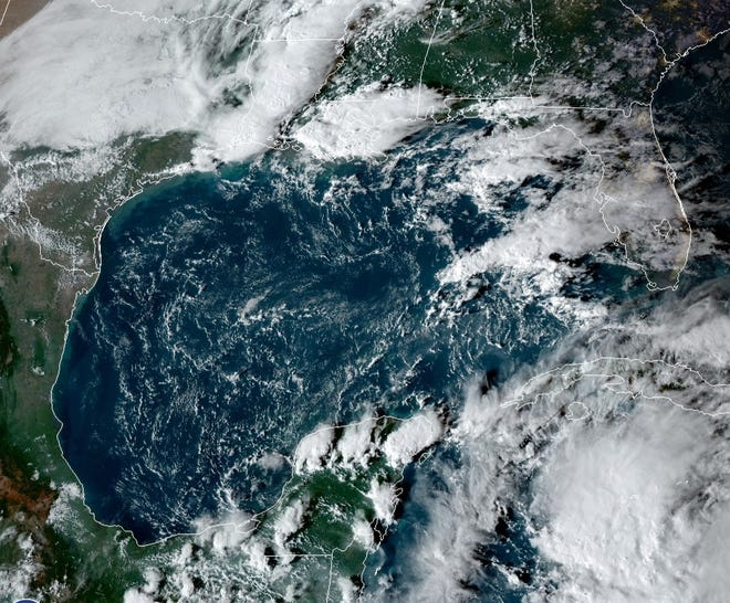 A satellite image shows a storm developing Friday afternoon in the Caribbean south of Cuba that forecasters say could enter the Gulf of Mexico Sunday or Monday.