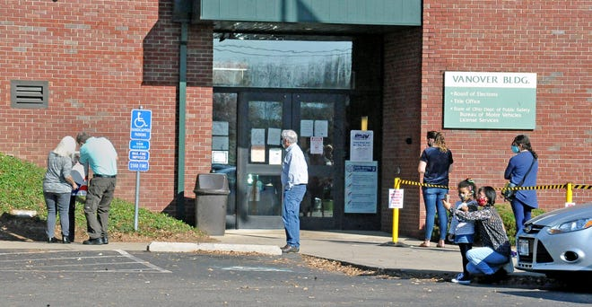A couple of people drop off their absentee ballots in the box outside the polling place in Wooster as others waiting to vote in person stand in line outside the building on Friday.