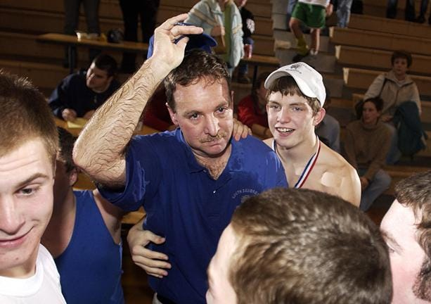 In a photo from 2003, South Davidson coach Mike Crowell celebrates with his wrestlers after leading them to the 1-A/2-A state championship.